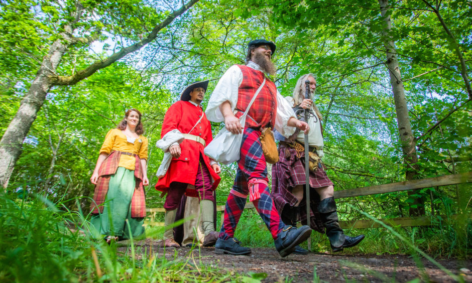 Walking through the woods, left to right are Saor Alba members Anne Delaforterie, Louis-Victor Phonyotha and Niko Magnus alongside John Neilson (enactor with Soldiers of Killiecrankie).