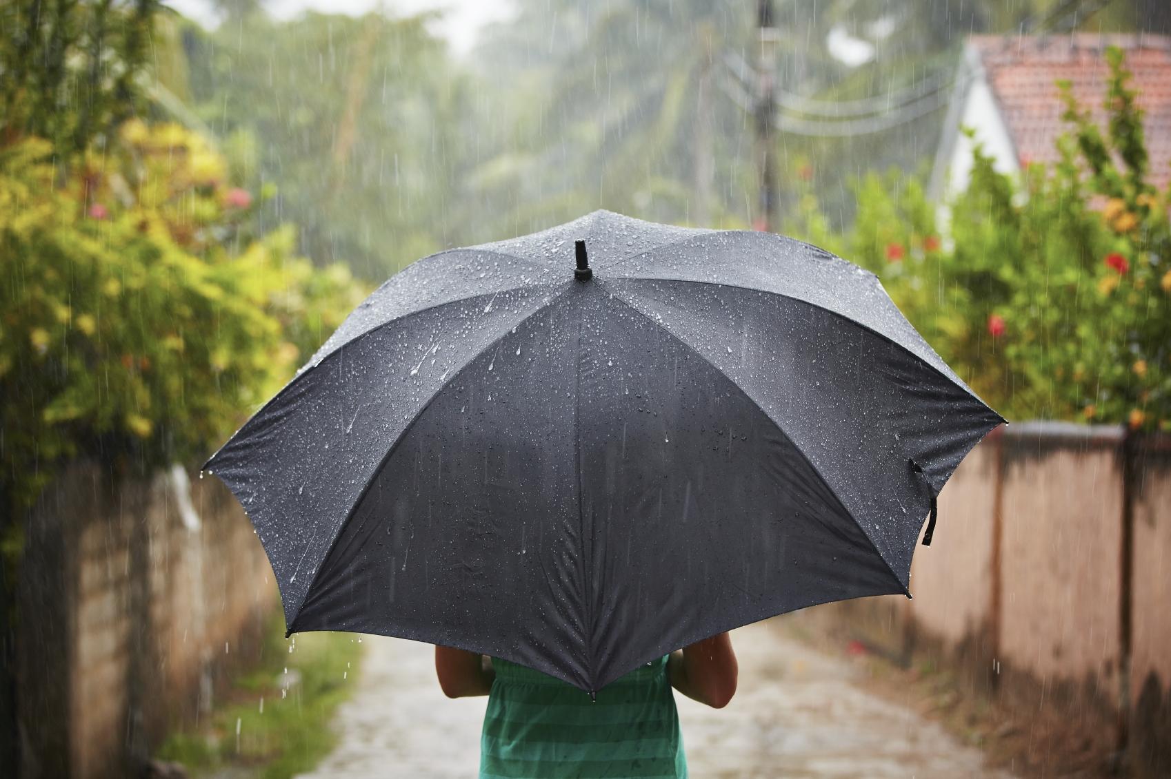 A woman with a black umbrella in heavy rain.