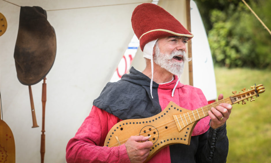 A man in medieval dress plays an instrument for the crowds.
