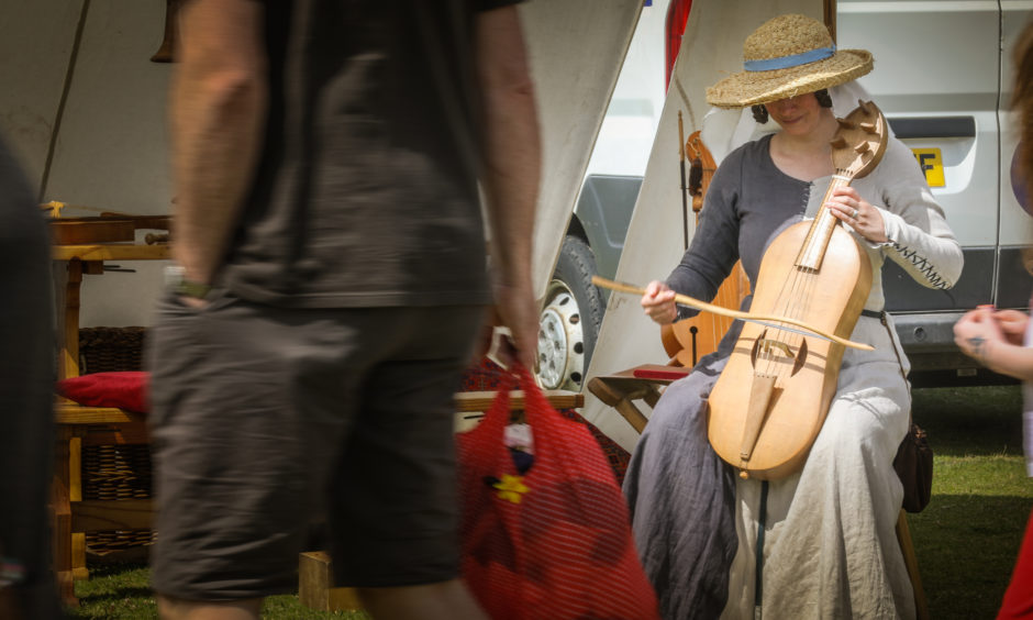 A lady in medieval dress plays an instrument for the crowds.