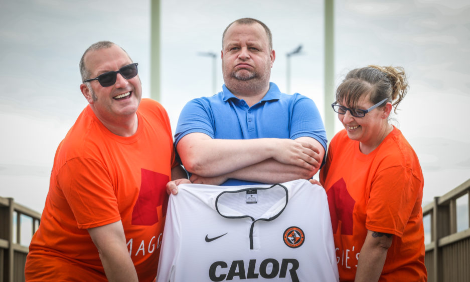 Dundee fan Scott Brown walks across Tay Road Bridge in a Dundee United top after losing a bet to United fans, Caroline and Stuart Main, that his side would not be relegated.