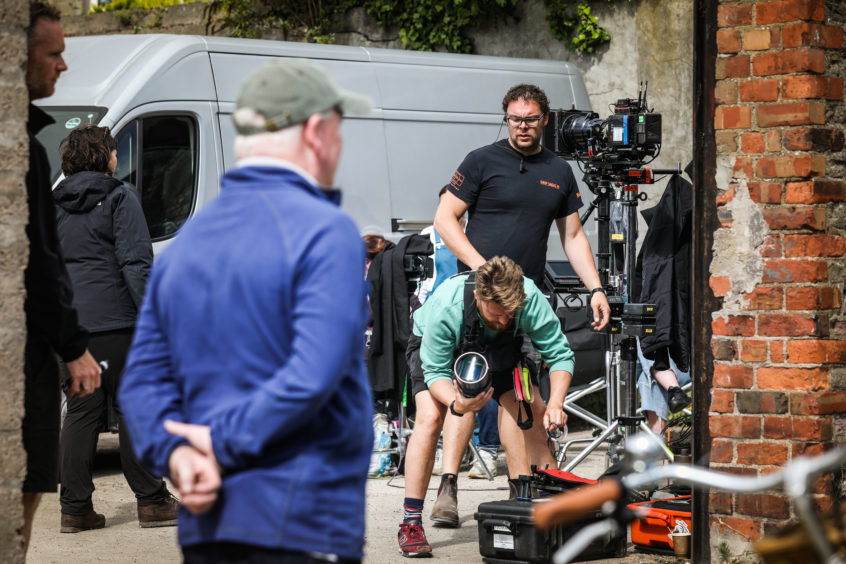 Camera crew and directors on set during filming.