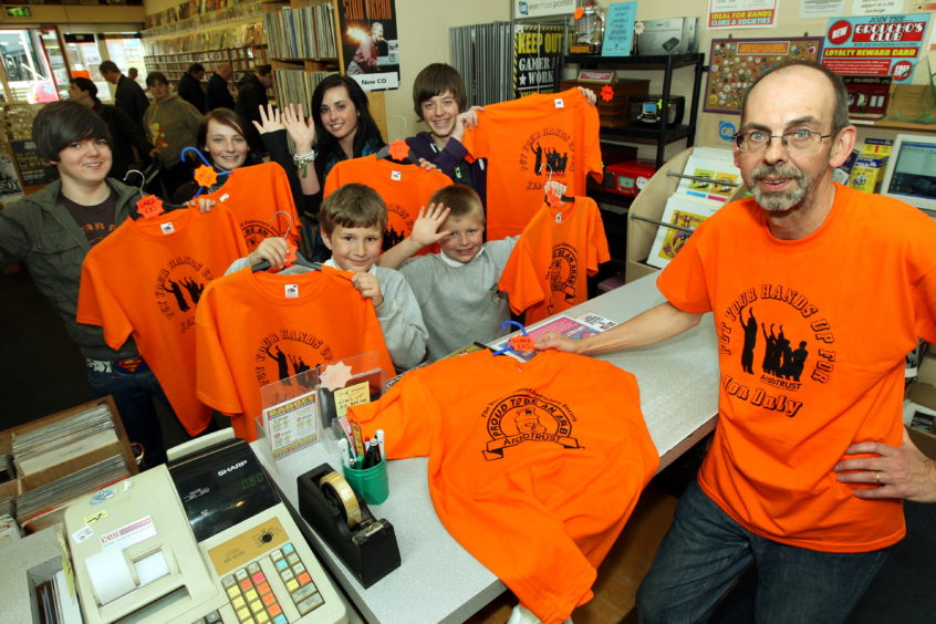 Alastair Brodie, owner of Grouchos with a group of kids in to buy their Dundee United shirts for the 2010 Scottish Cup FInal.