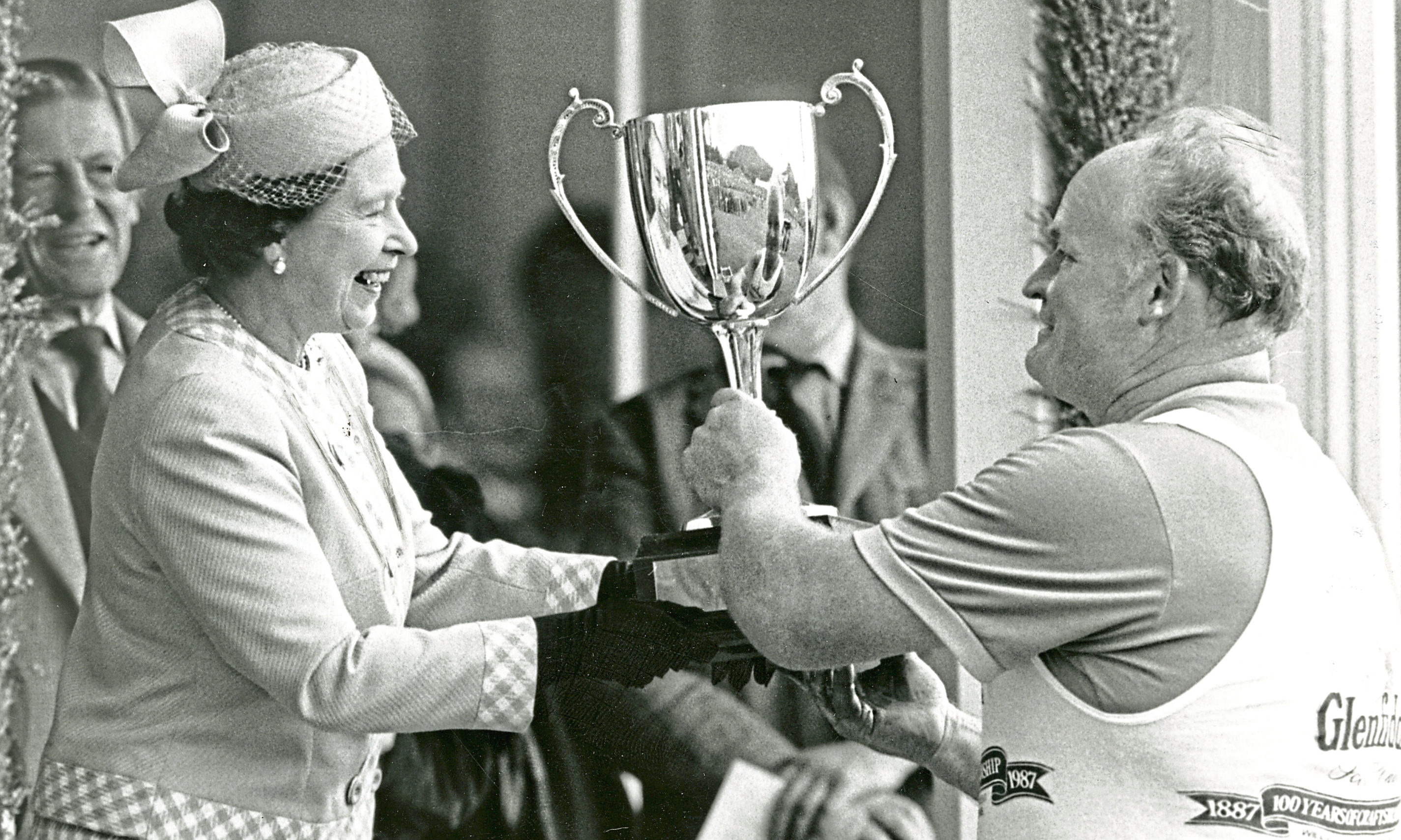The Queen presents a trophy to Bill Anderson at the Braemar Gathering in 1987.