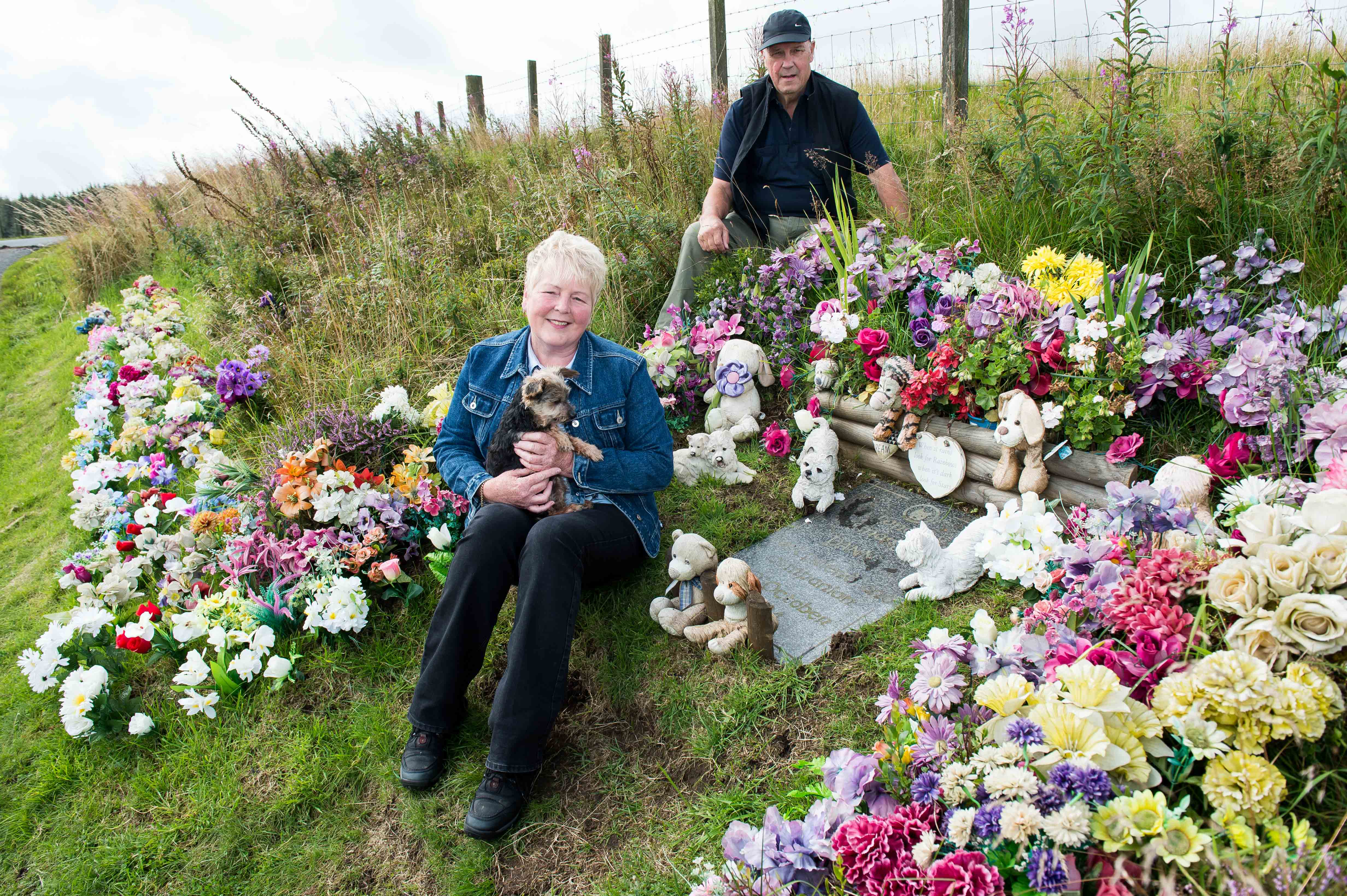 Moira Campbell and her dog, Rusty, with William Robertson, who tends to the grass and flowers at the roadside grave of 'Danny' near Loch Glow