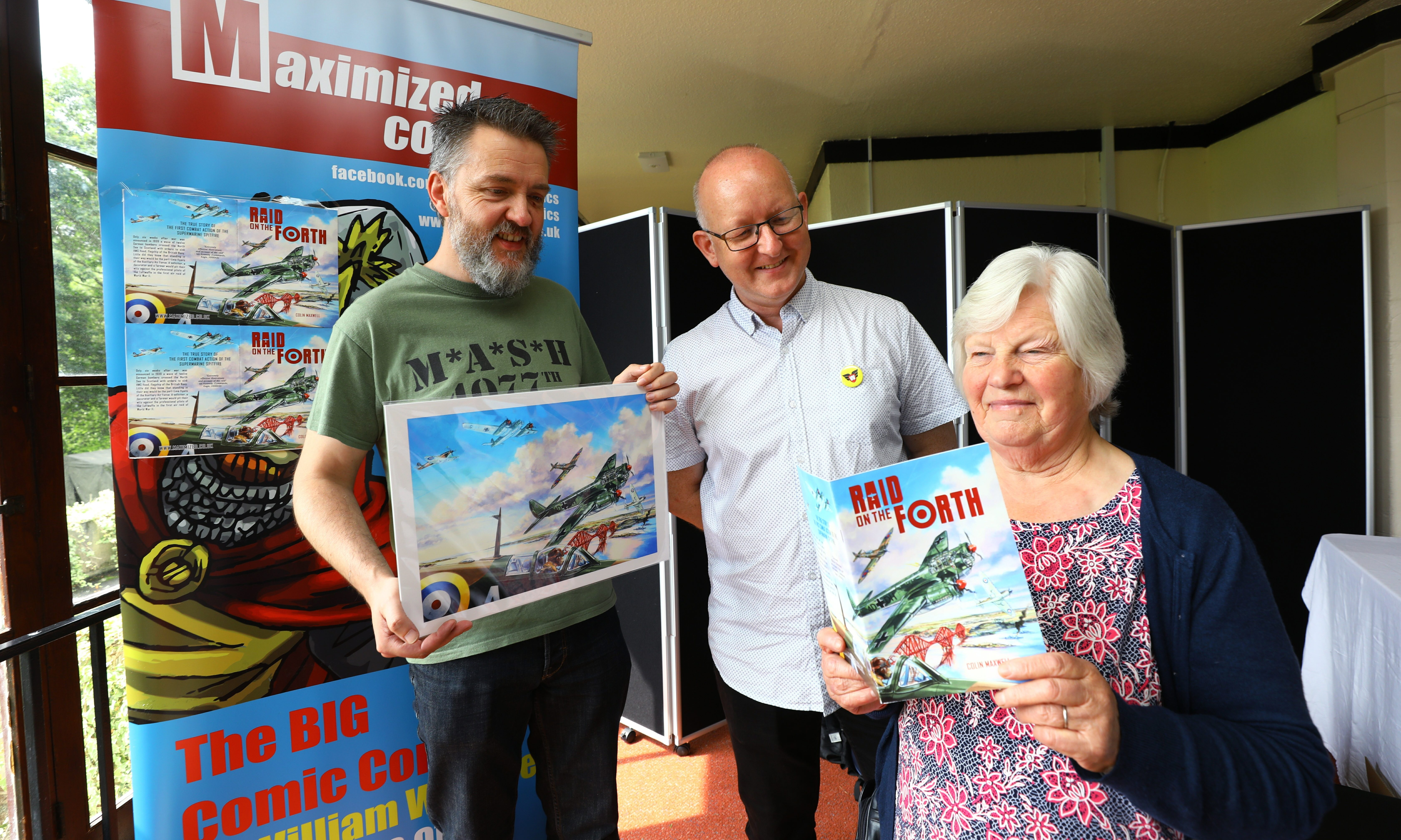 Margot Allison with the book with author Colin Maxwell, centre, and artist Graeme Neil Reid,