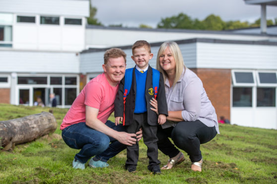 Daniel is pictured outside the school with mum Louise Paton and Dad Nicky Cornet.