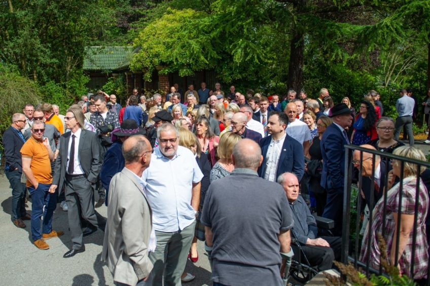 Mourners gather ahead of the funeral ceremony.