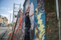Sabien works on an Oor Wullie mural