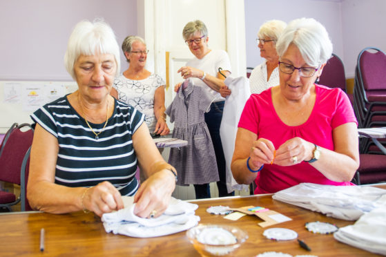 Dorothy Bruce and Ann Menmuir, front, mend uniforms ahead of the opening of Forfar's pop-up shop, aided by fellow volunteers Diane Robertson, Lynne Morrison and Muriel Drummond.