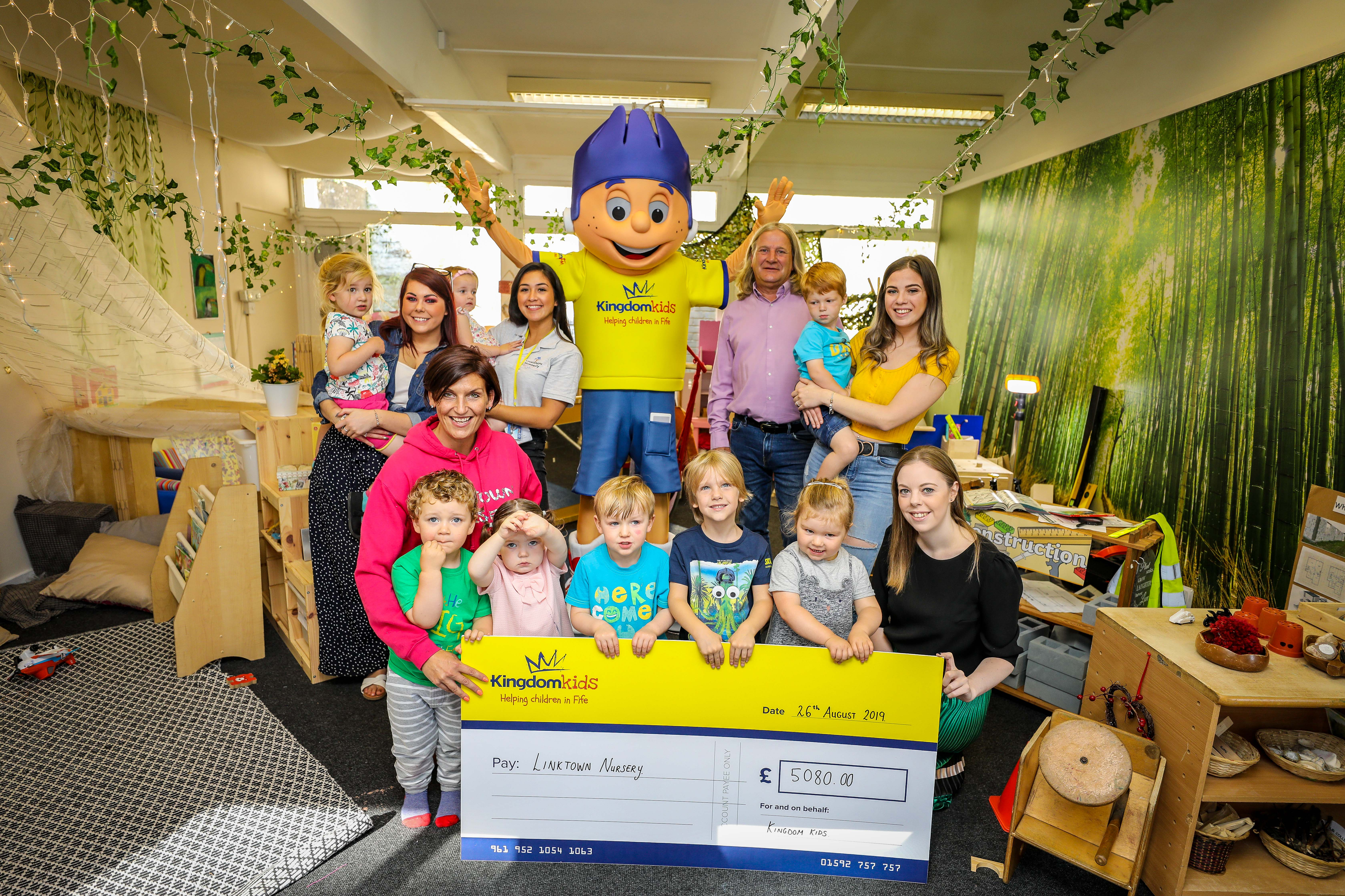 Linktown Nursery in Kirkcaldy was awarded £5080 in goods for the nursery. Staff and kids who use the service along with Kingdom Kids Mascot.
