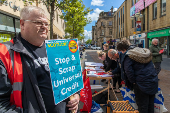 John Gillespie of Unite the Union holds a plackard as people sign an Anti Universal Credit petition.