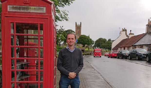 Stephen Gethins outside the phone box in Kilconquhar.