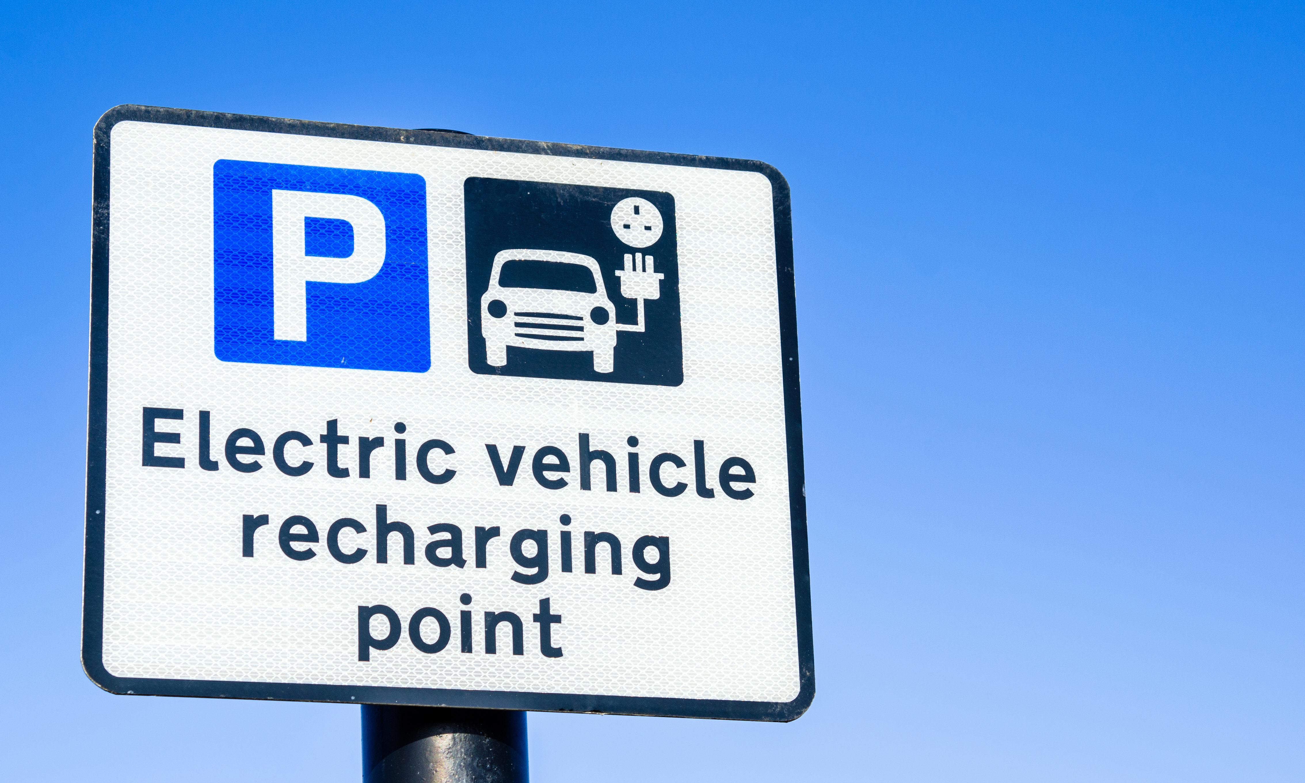 Parking Sign at a Recharging Station for Electric Vehicles and Clear Blue Sky