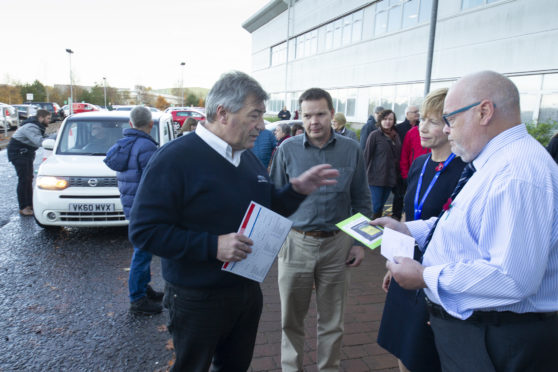 Parking protester Barrie Ewart handing over his petition against parking charges to administration leader  councillor David Fairweather.