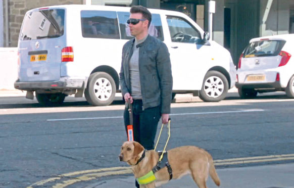 Des Clarke in Broughty Ferry with a guide dog.
