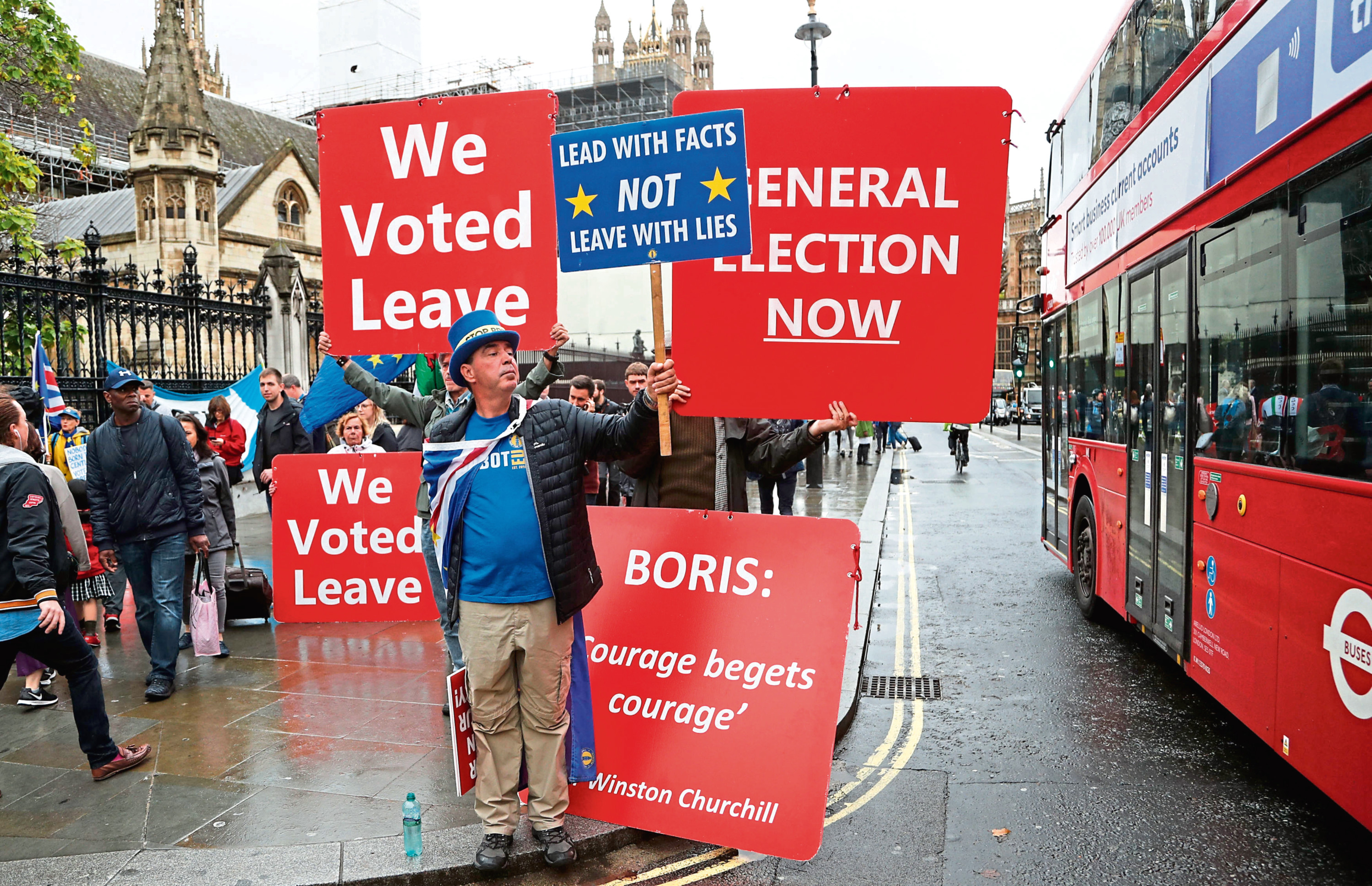 Pro and anti-Brexit supporters hold signs and demonstrate outside Parliament in London.
