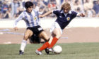 Argentina's Diego Maradona (left) with Asa Hartford at Hampden during an international fixture against Scotland.