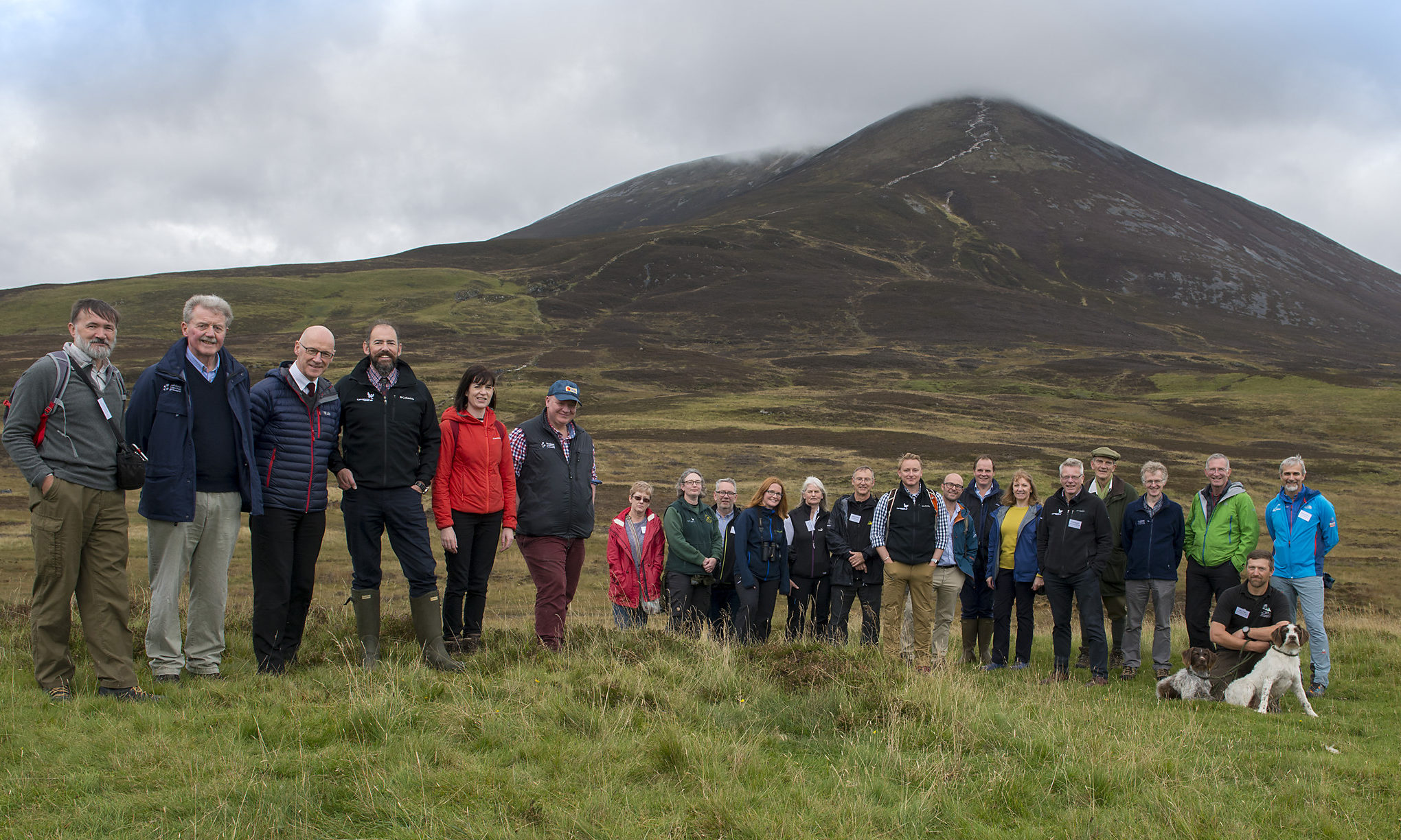 Photo, MSP John Swinney after the ribbon with the Beinn a Ghlo mountain behind Flanked by Left, Ian Moffett OATS Chair, Outdoor Access for Scotland, & right Doug McAdam, CNPA board Member , with other guests and partners.