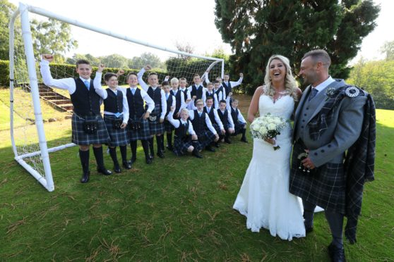 Callum and Danielle on their wedding day with the Fair City FC under-13s squad