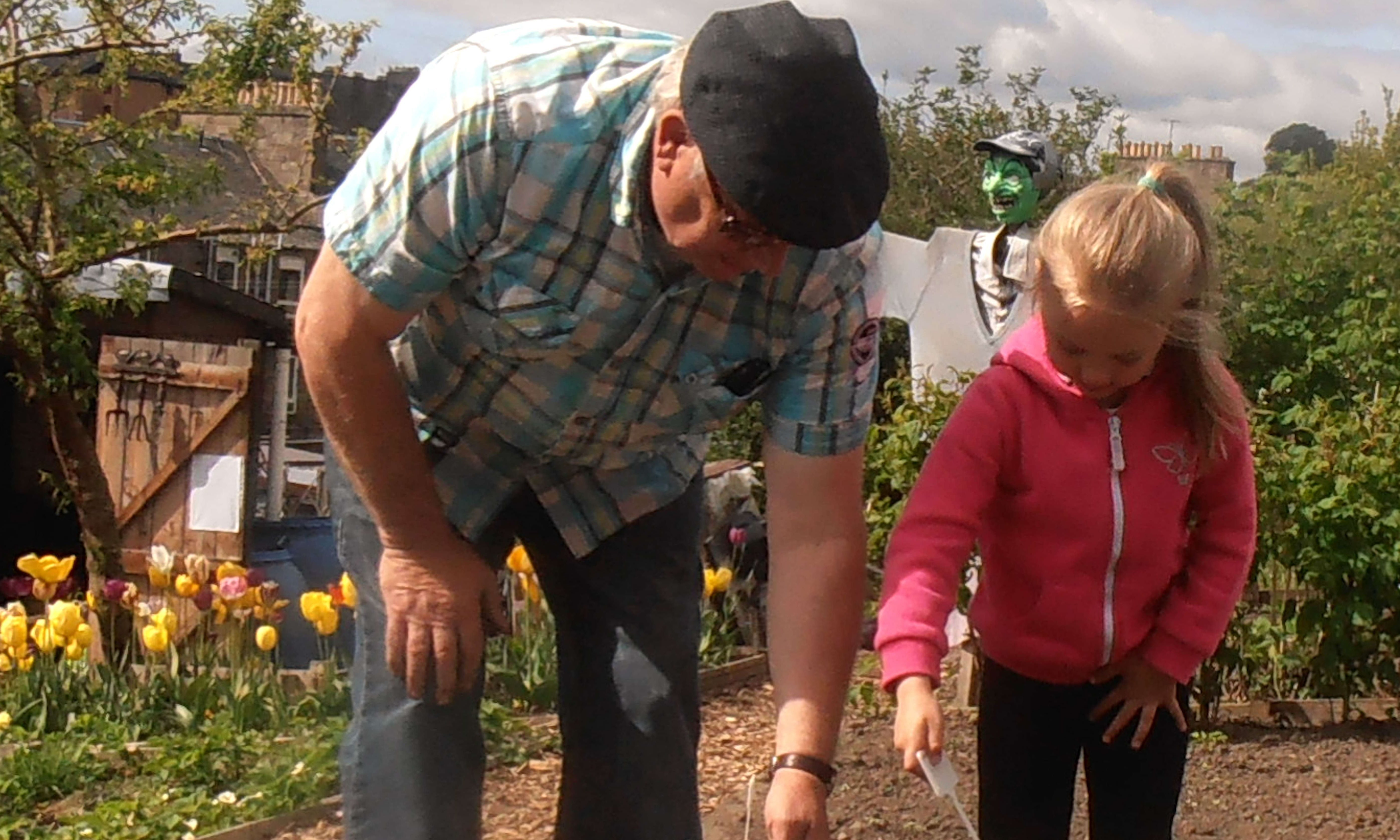 Grandad helping Scarlet plant her pumpkins