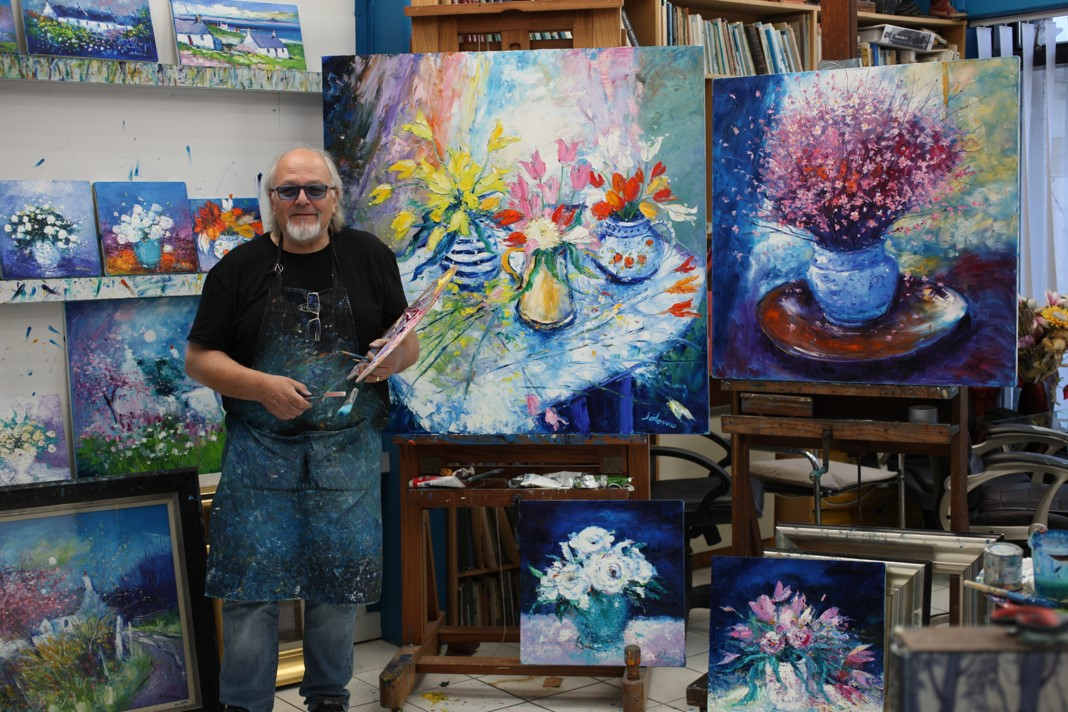Jolomo with some of his paintings.
