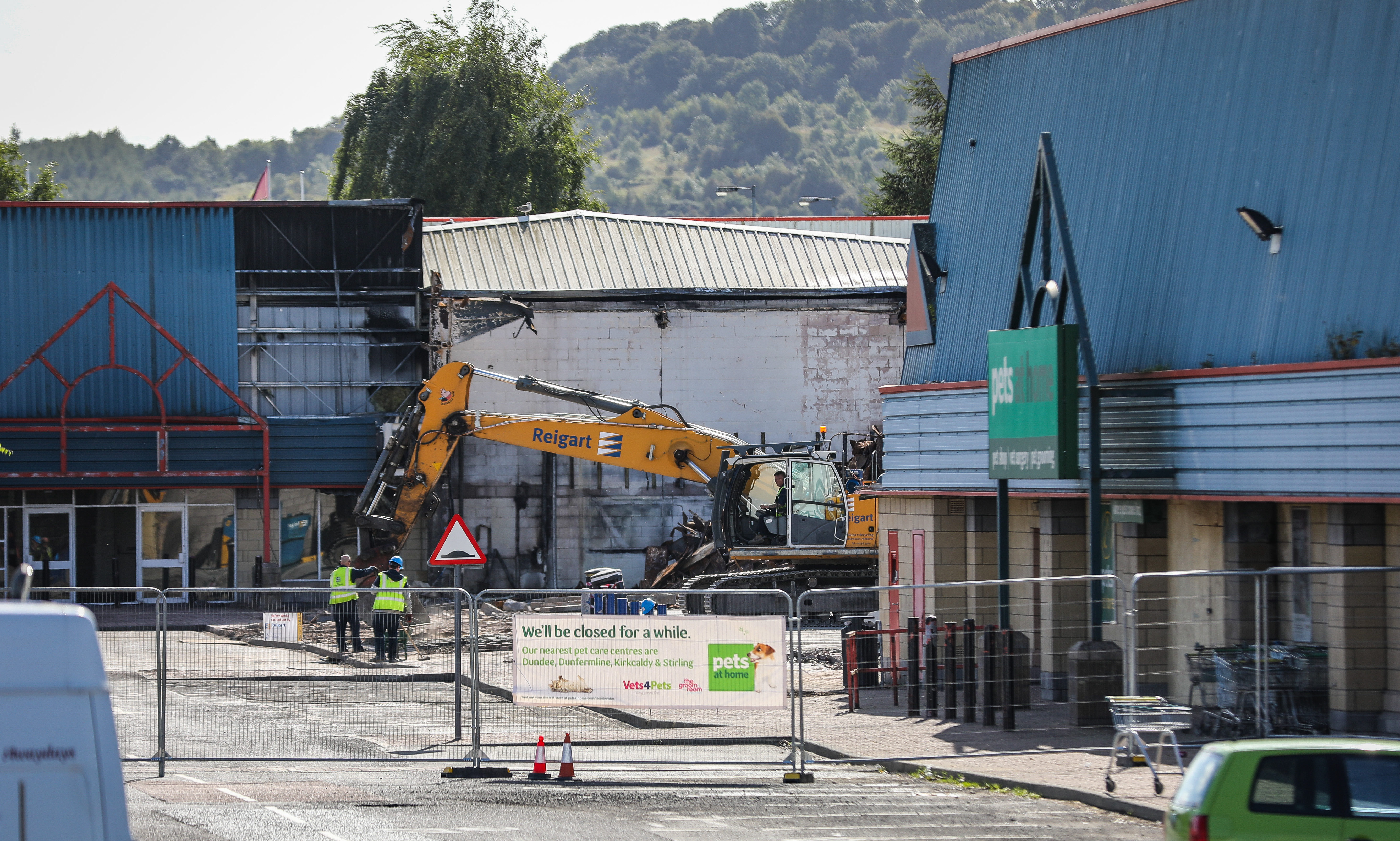 Bulldozers level the site of the B&M building, after last month's fire