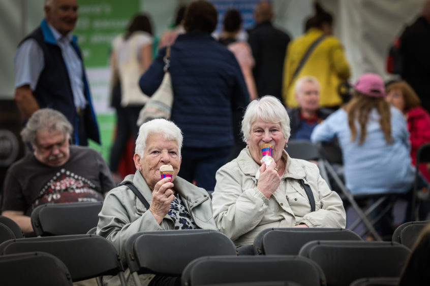 Two ladies have an ice cream while they wait for another cooking demo.