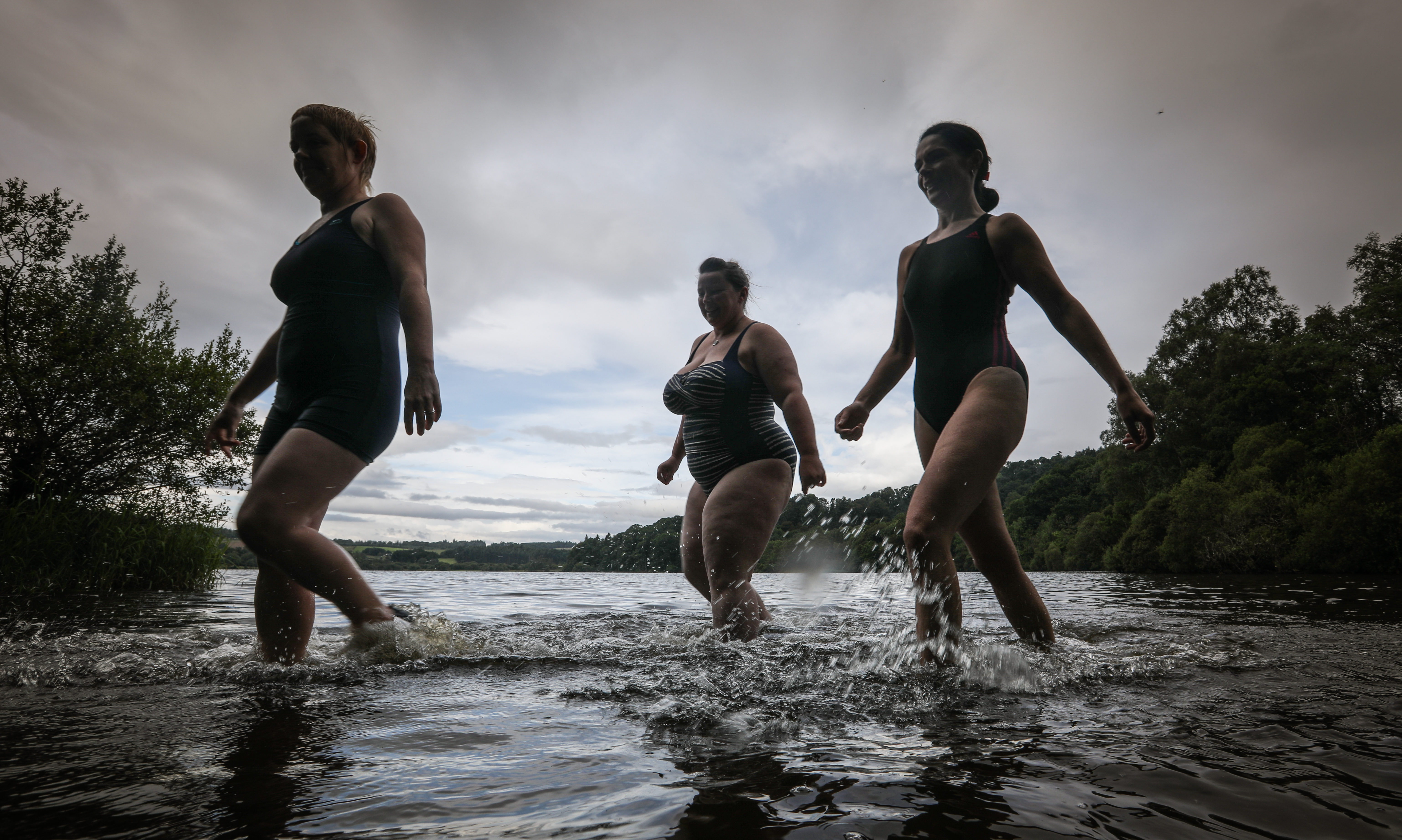 Gayle, right, enters the chilly waters of Clunie Loch with Kelly McIntyre and Mel Chadd.