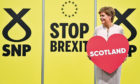 "First Minister of Scotland and SNP leader Nicola Sturgeon holds a heart-shaped placard reading ""Scotland"" at the party autumn conference on October 14, 2019."