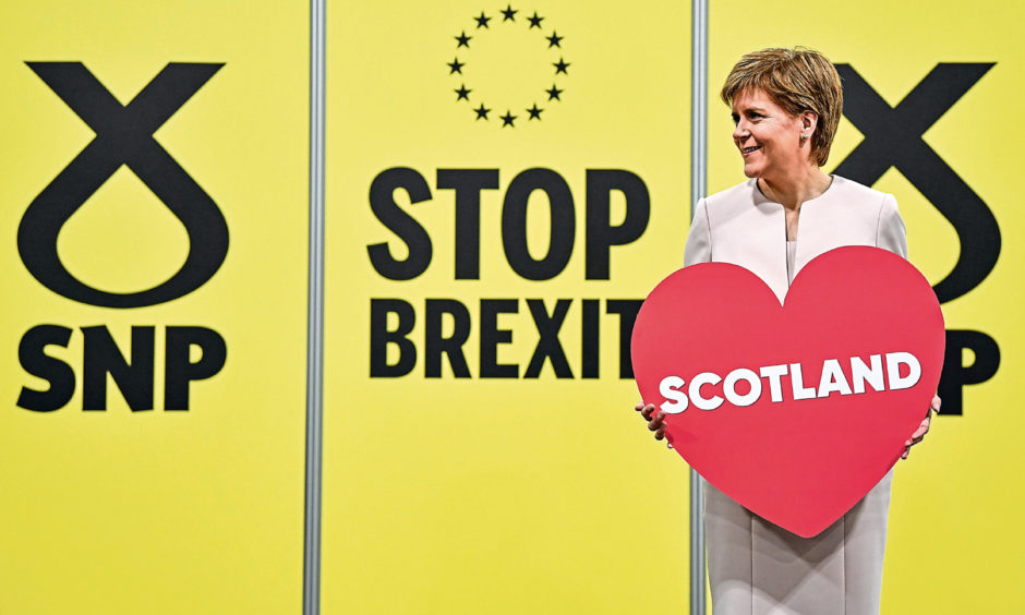 """First Minister of Scotland and SNP leader Nicola Sturgeon holds a heart-shaped placard reading """"Scotland"""" at the party autumn conference on October 14, 2019."""