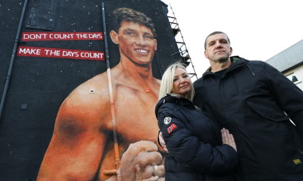 Connor Law's parents Kaye and Gary Law beside the mural of their son.