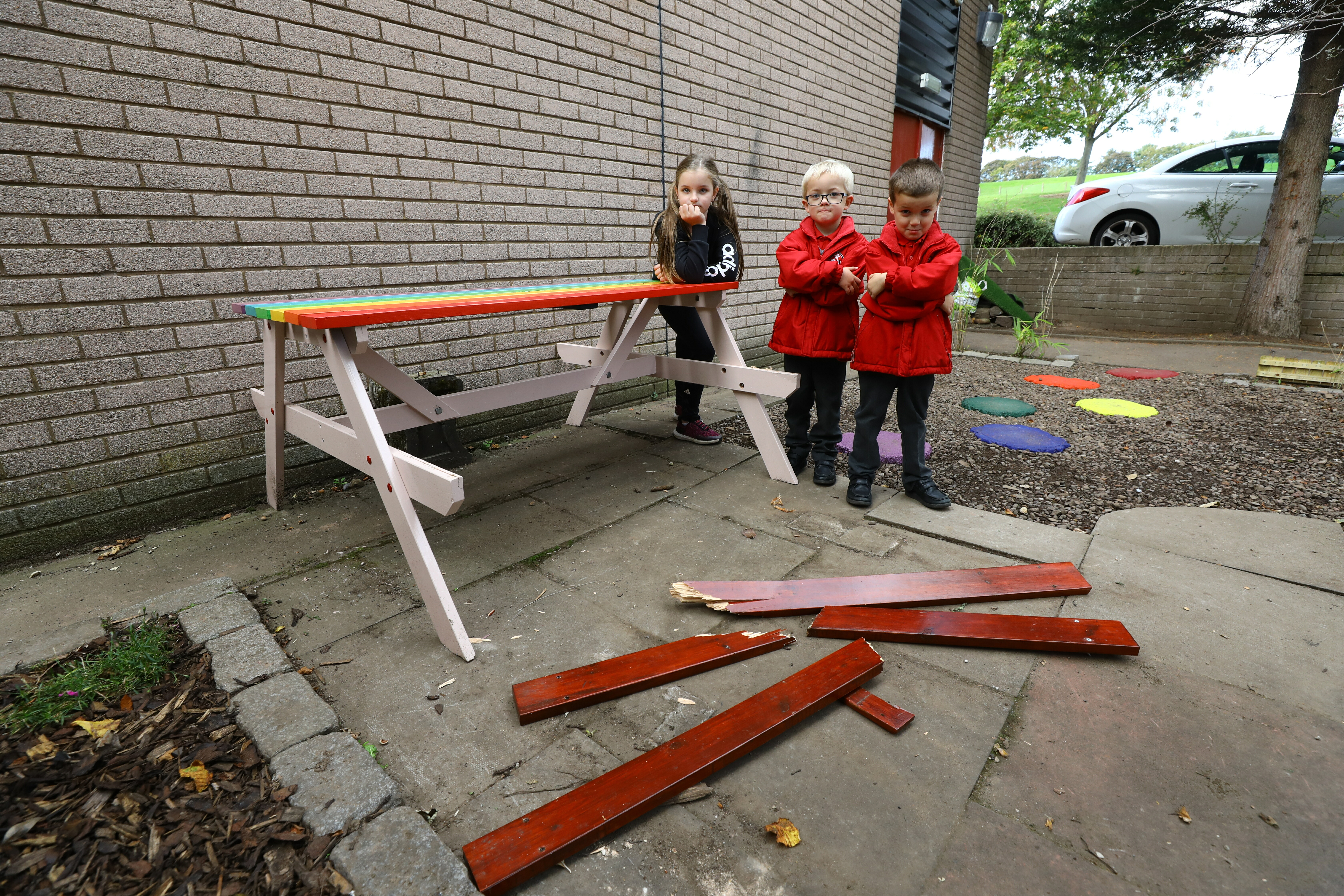 Jessica Craik, Jamie Ritchie and Theo Craik beside the vandalised bench in the sensory garden at Craigiebarns Primary School, Dundee.
