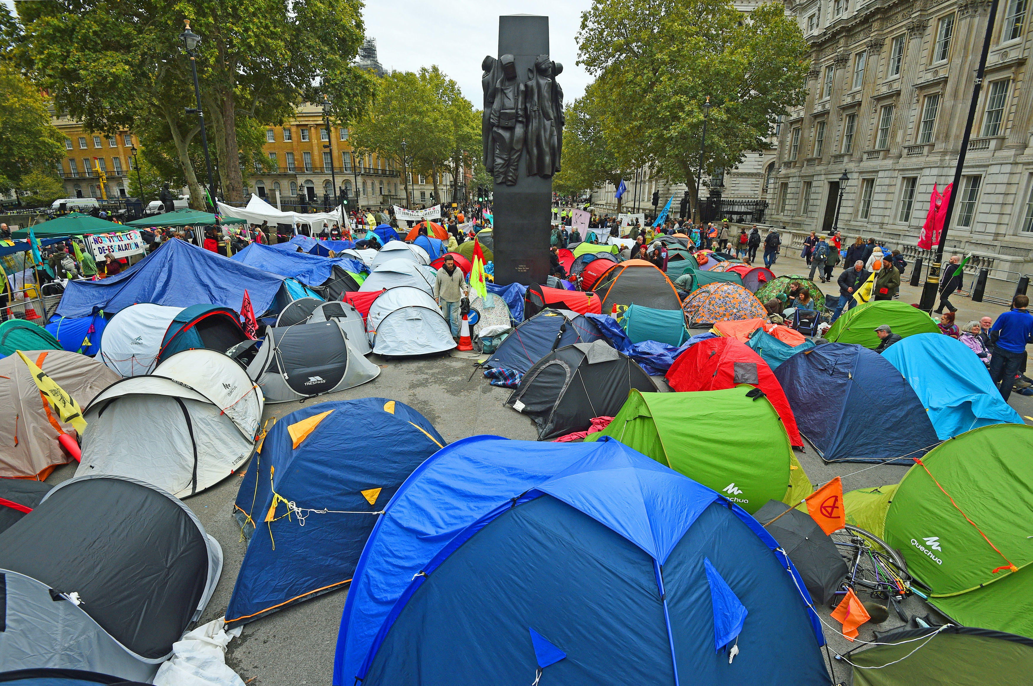 Extinction Rebellion (XR) protesters camp in tents around the Monument to the Women of World War II on Whitehall in Westminster, central London.