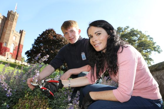 Apprentice gardener at Scone Palace Kieran Bruce shows Gayle how to prune some flowers.
