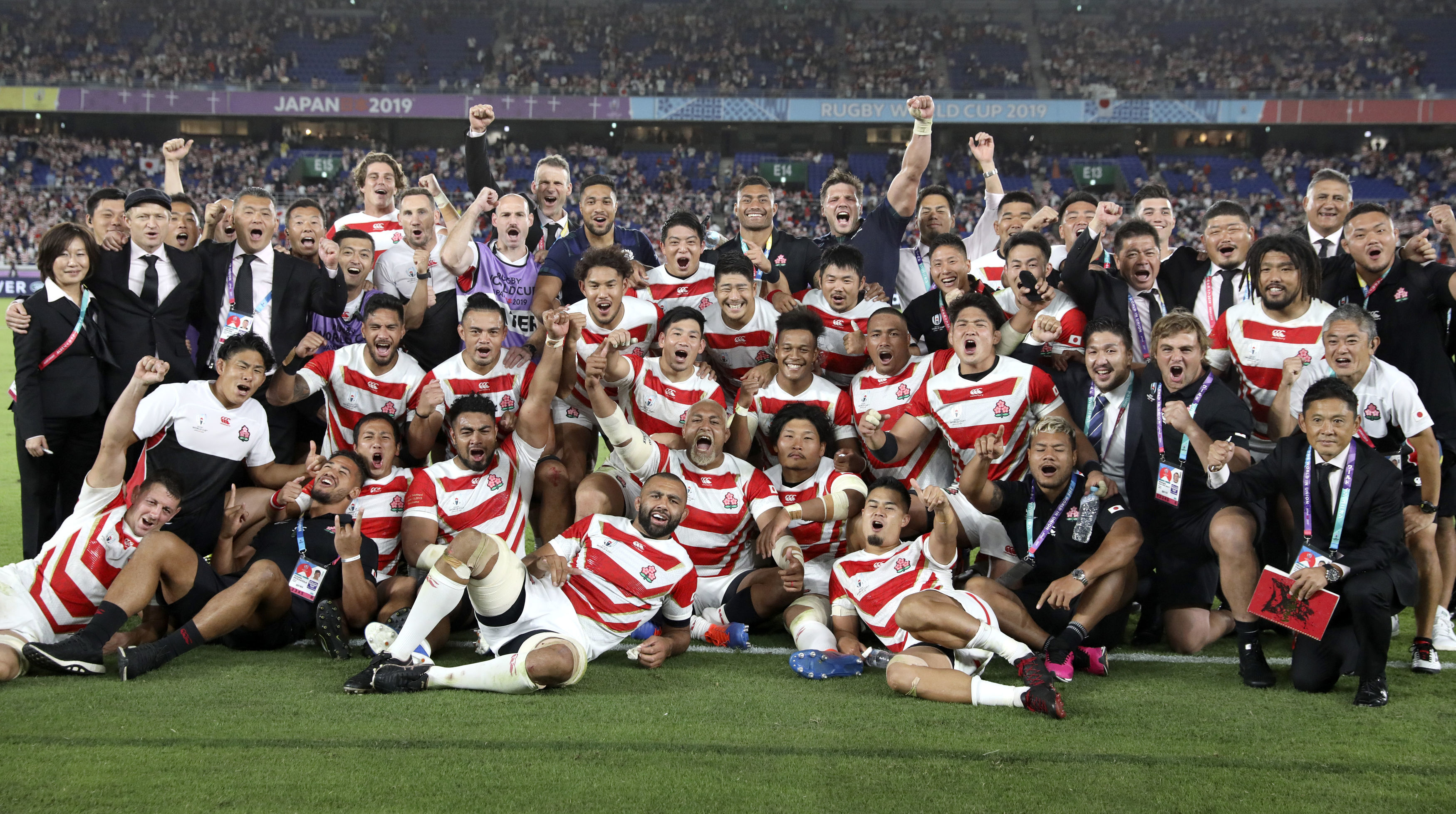 Japan players and management celebrate after defeating Scotland.