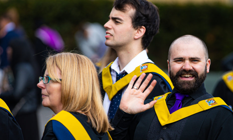 A student gives a coy wave and a smile as he heads into graduation.