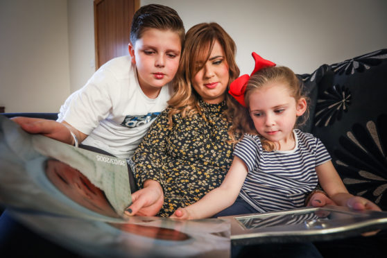 Zach Kyles, 11, Nadia Wright, 32 and Sofia Neish, 4, looking at pictures of son Brandon Kyles.