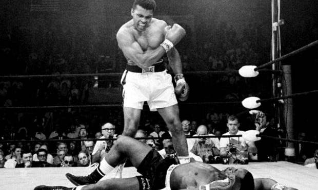 Heavyweight champion Muhammad Ali stands over fallen challenger Sonny Liston, after dropping Liston with a short hard right to the jaw in Lewiston, Maine.
