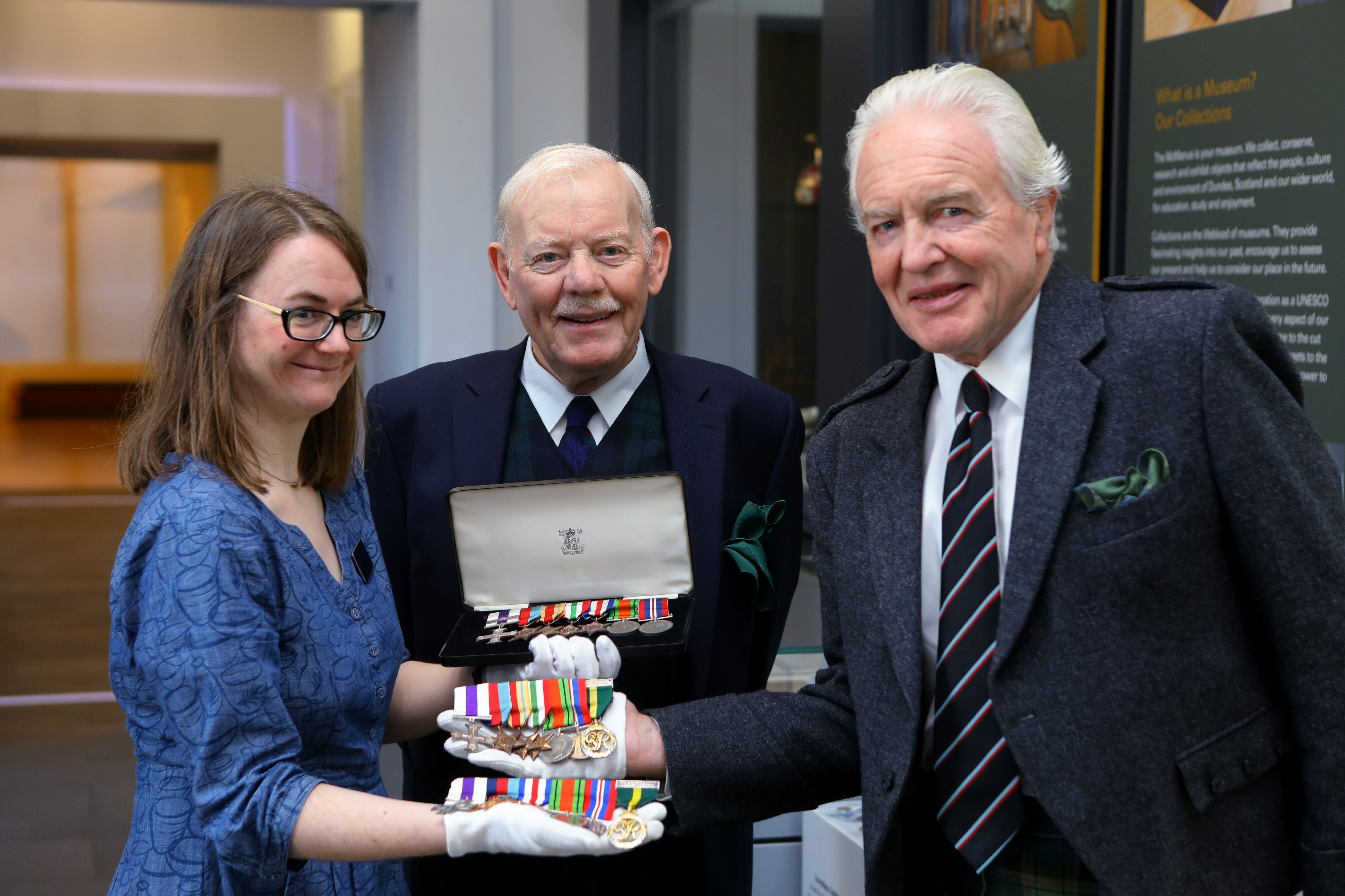 Carly Cooper, Curator, with Ian Rae, right, and Sinclair Aitken, centre, Chairman of LACD, holding the medals that were handed over to the McManus Galleries.
