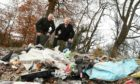 Mr Caldwell, left, and Mr O'Brien inspect some of the rubbish.