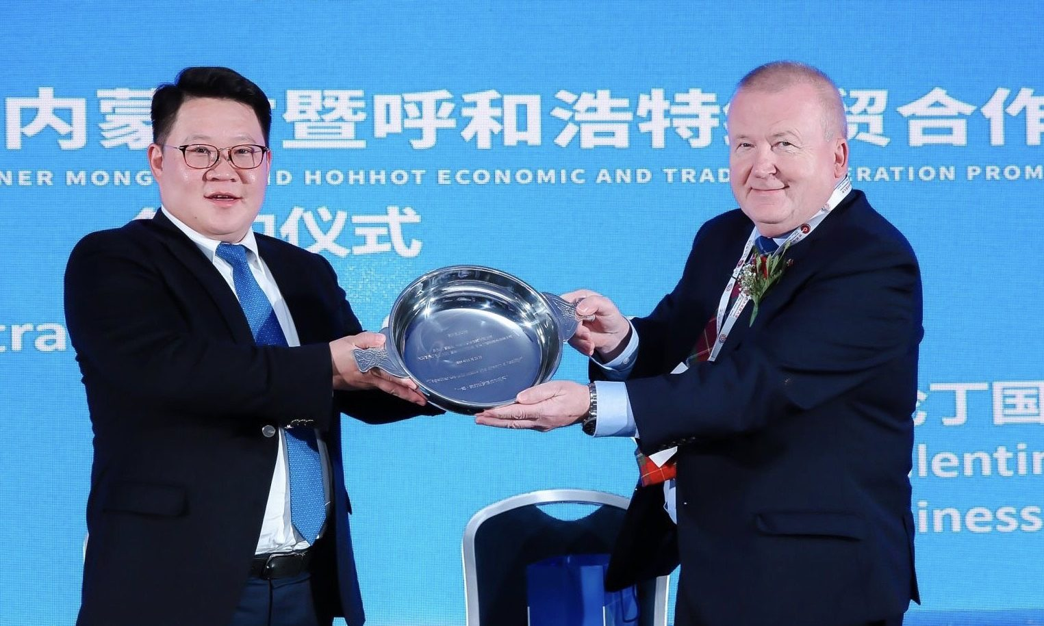 "MengTai vice-chairman Ao Bo and Angus businessman Dave Valentine holding a quaich inscribed with the message ""Together we will make the dream a reality""."