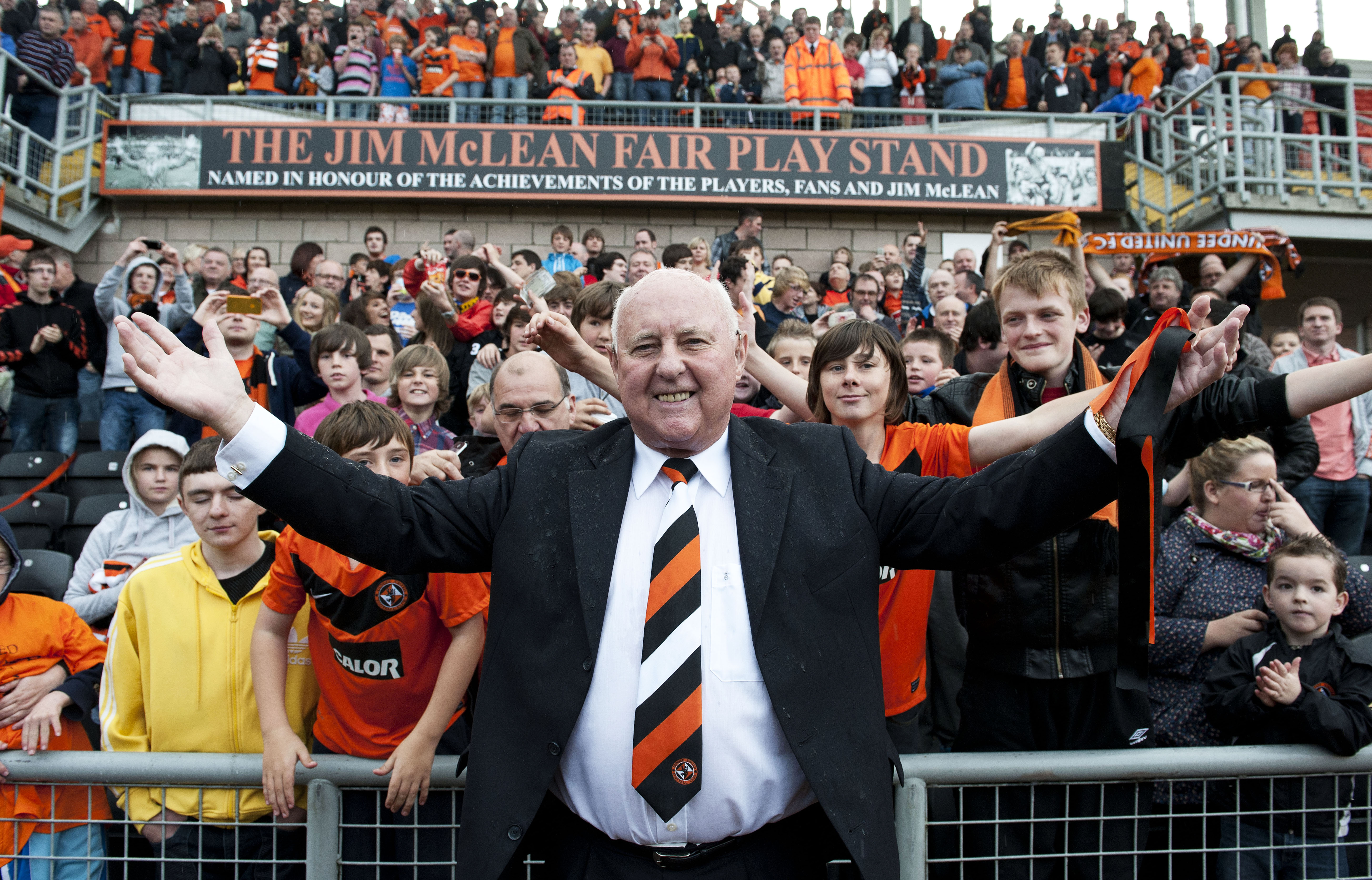 Dundee United legend Jim McLean celebrates with fans after a stand at Tannadice is named after him in 2011.