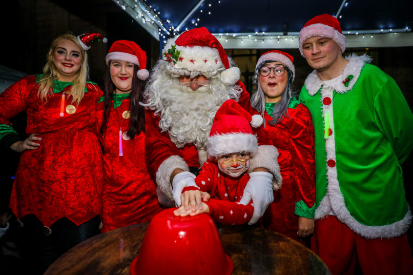 Findlay Spence (6) from Markinch switches on the Christmas Tree lights with the help of Santa and his elves.