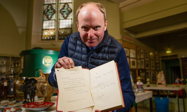 Auctioneer Nick Burns with the book and letter signed by Winston Churchill