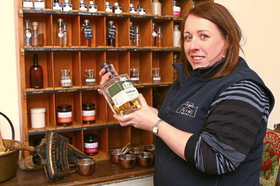 Gin Bothy founder Kim Cameron holding a bottle of gunshot gin.