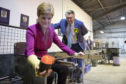 SNP leader Nicola Sturgeon, with SNP candidate for Ochil & South Perthshire, John Nicolson, makes a glass paperweight at Caithness Glass during a visit to Crieff Visitors Centre