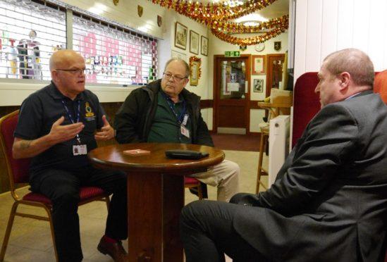 Veterans Minister Graeme Dey meets Legion Scotland volunteers (left to right) Paul Jones and Robert Holland at the Forfar branch of Legion Scotland.  Both are also veterans.