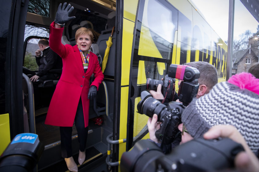 SNP leader Nicola Sturgeon boards the party's campaign bus outside the Scottish Parliament, Edinburgh, on the last day of the General Election campaign trail in 2019.
