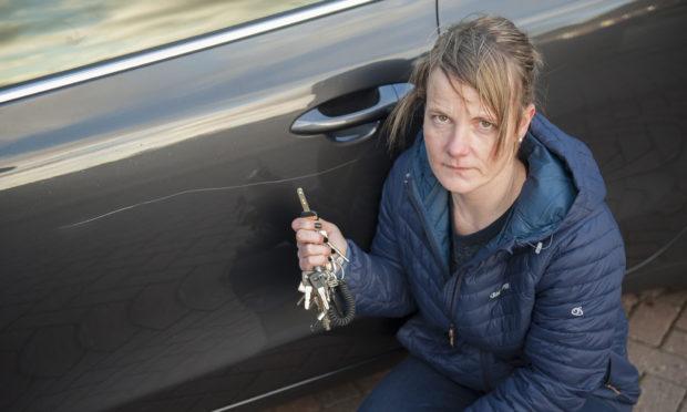 Nikki Murray, a volunteer driver for Contac the Elderly, beside the vandalism.